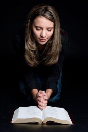 inginocchiarsi: Donna Pregare Con Bibbia