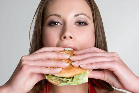 Woman Eating Hamburger Imagens