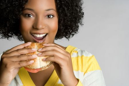 Happy Young Woman Eating Burger Stock Photo - 5668628