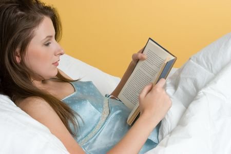 Girl Reading Book in Bed