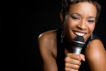 Black Woman Singing into Microphone Stock Photo