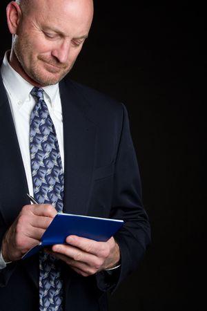 Handsome bald businessman writing check