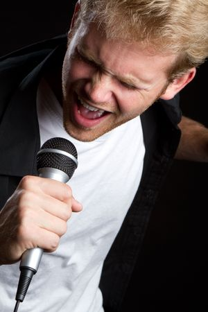 Young man sining into microphone Imagens
