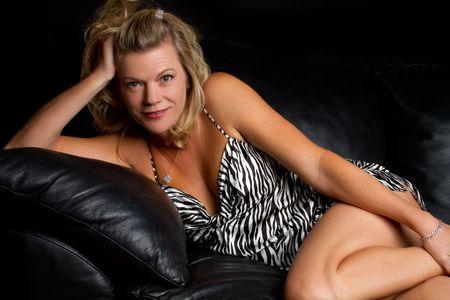 vecchiaia: Bella donna sul divano in pelle