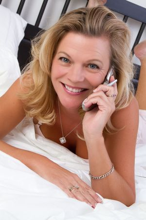Woman on bed talking on phone Stock Photo - 7076941