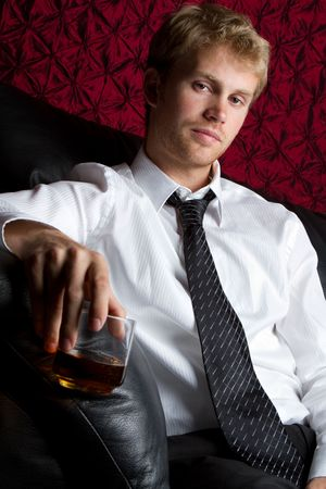 Young man drinking scotch alcohol
