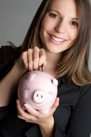 Woman dropping coin in piggy bank Stock Photo - 7172725