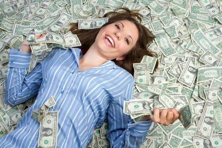 playing with money: Woman laying in money
