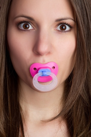 Beautiful young woman sucking pacifier Фото со стока