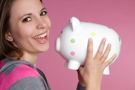 Pretty girl holding piggy bank Stock Photo - 9105736