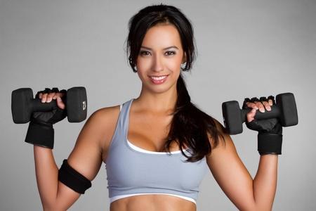 美しいラテン女性の持ち上がる重量