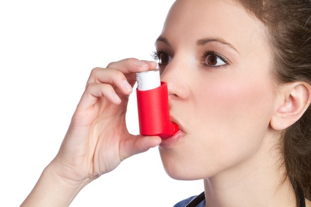 bronchial: Pretty girl holding asthma inhaler LANG_EVOIMAGES