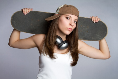 Pretty skater girl holding skateboard Stock Photo - 9105774