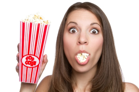 Beautiful young girl eating popcorn