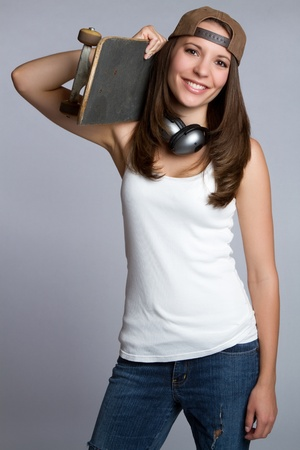 Smiling skater girl holding skateboard Stock Photo - 9105773