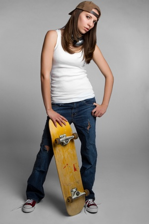 Pretty skater girl holding skateboard Stock Photo - 9105770