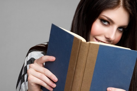 Pretty teen girl reading book