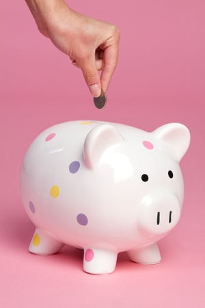 Person dropping coin into piggy bank Stock Photo - 9397182