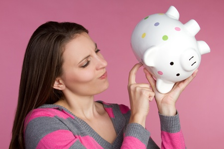 Young woman holding piggy bank Stock Photo - 9397197