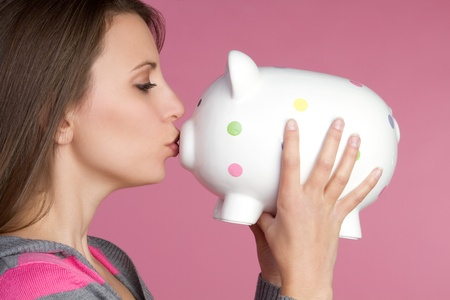 Pretty girl kissing piggy bank Stock Photo - 9397193