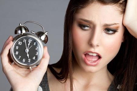 Annoyed woman holding alram clock Standard-Bild