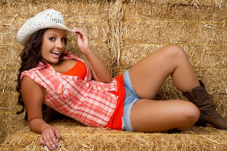Beautiful smiling cowgirl in hay Stock Photo - 9466125