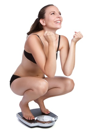 crouching: Weight loss woman on scale LANG_EVOIMAGES