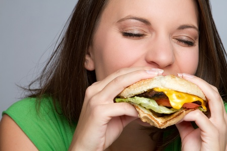 Beautiful girl eating hamburger food Фото со стока