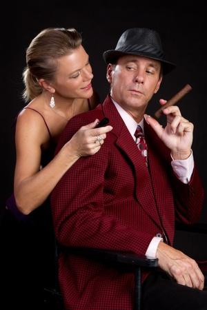 Woman lighting cigar for man