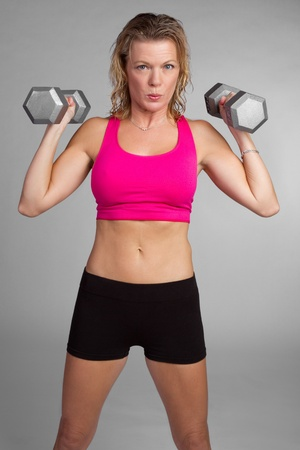Middle-aged fitness woman lifting weights photo