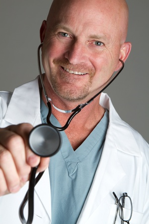 Smiling handsome doctor holding stethoscope photo