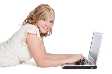 Smiling blond woman using laptop photo