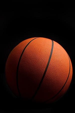 lowkey: Orange basketball on black background Stock Photo