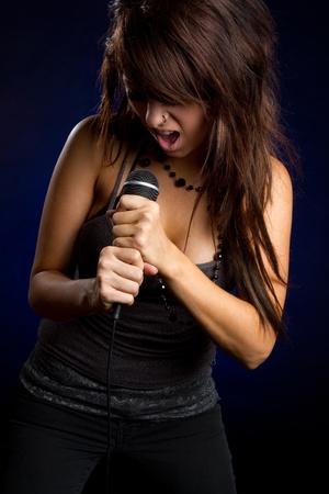 kareoke: Rockstar girl singing holding microphone LANG_EVOIMAGES