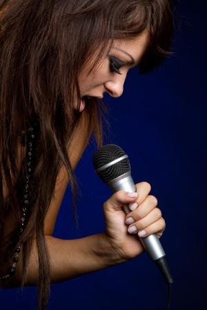 kareoke: Beautiful microphone singing rockstar girl LANG_EVOIMAGES