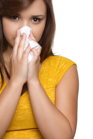Hispanic teen girl blowing nose Stock Photo - 10559480