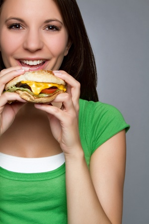 Beautiful young woman eating hamburger Фото со стока