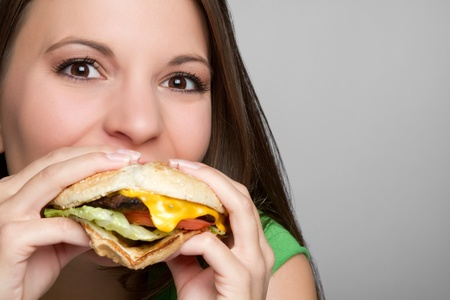 adult sandwich: Beautiful girl eating hamburger food LANG_EVOIMAGES