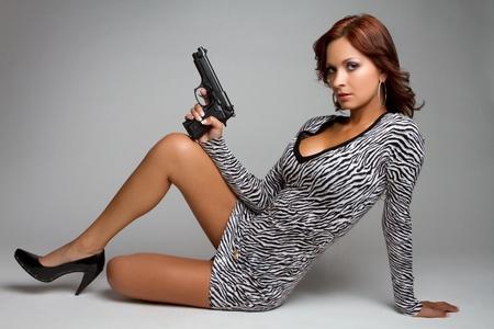 tight dress: Sexy latin woman holding gun
