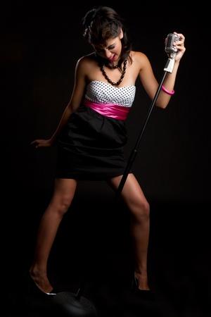 kareoke: Hispanic woman singing into microphone LANG_EVOIMAGES