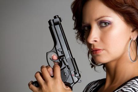 Sexy woman holding hand gun photo
