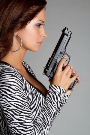 Beautiful woman holding hand gun photo