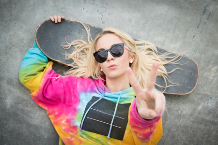 peace sign: Pretty blond skater girl giving peace sign