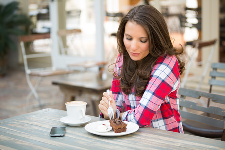 美しい女性がカフェでチョコレート ケーキを食べて