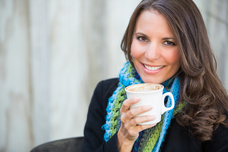 20 30: Beautiful smiling woman drinking cup of coffee