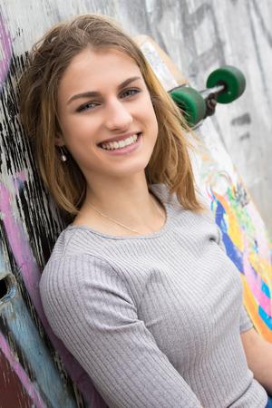 Smiling teen girl with skateboard Standard-Bild