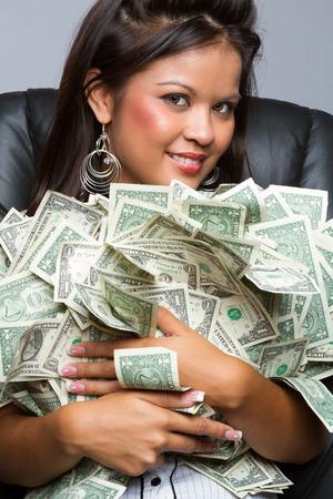 Beautiful woman holding pile of money photo