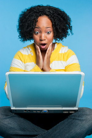 Shocked black woman using laptop computer photo