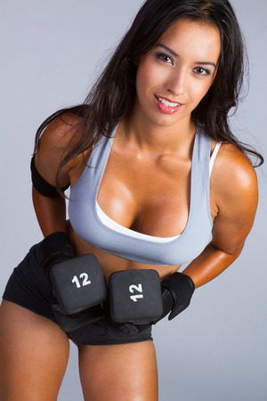 Latin American fitness woman lifting weights photo