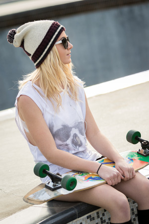 blonde teenager: Pretty blond skater girl holding skateboard